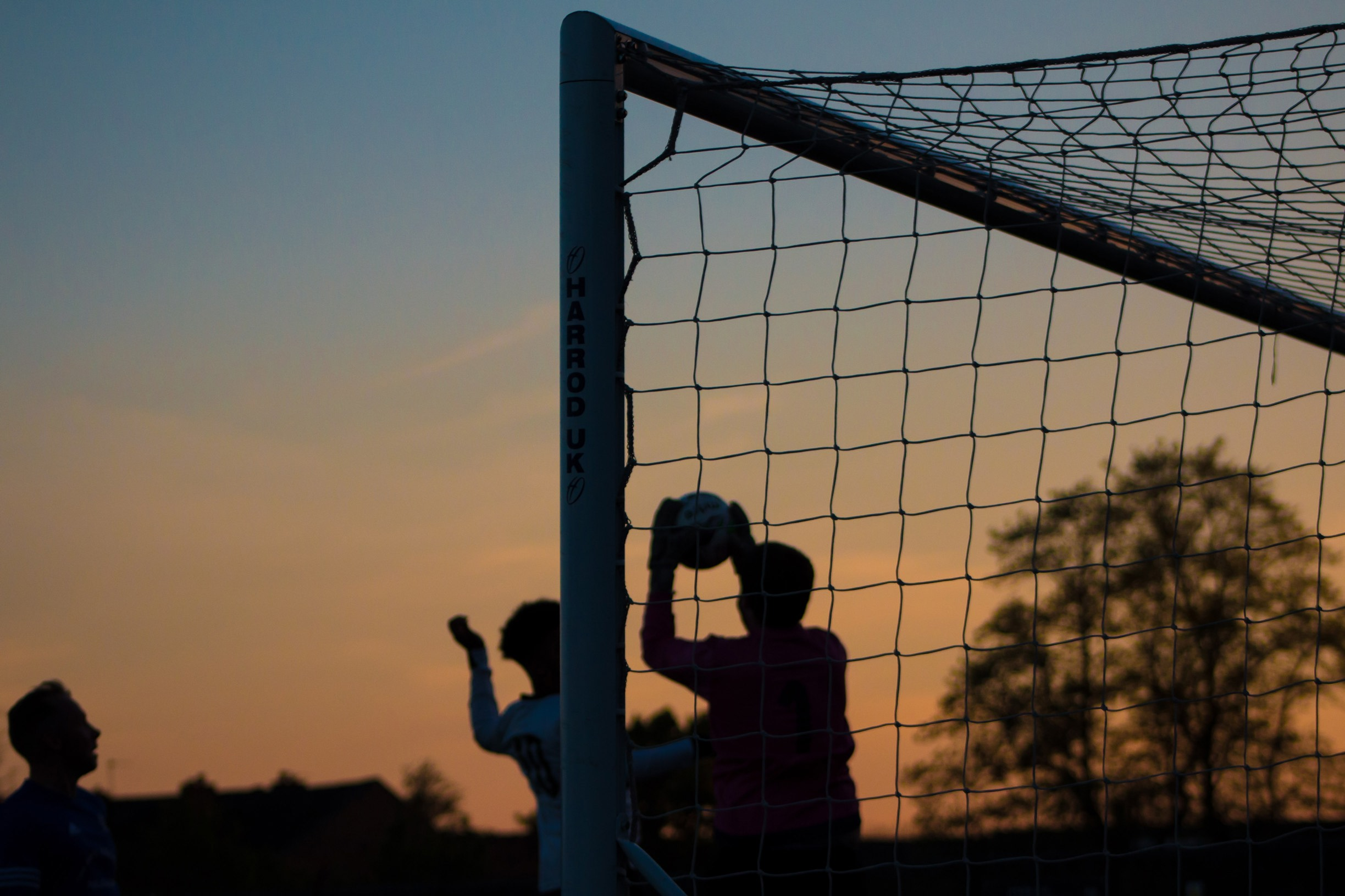 A goalkeeper saves a goal, silhouetted against a sunset