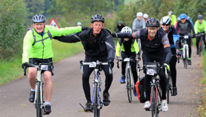 three male cyclists link arms while cycling their bikes on a country road