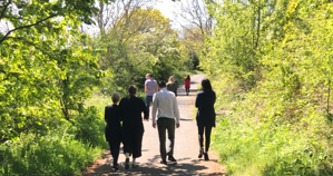 A group of people walk along a park path
