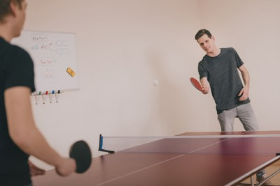 Two young men playing table tennis