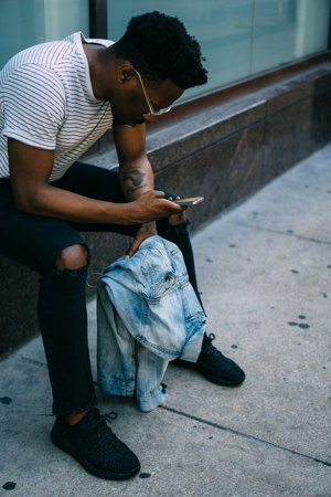A young man sits on a doorstep hunched over a phone