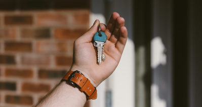 A persons hand holds up a house key against a brick background