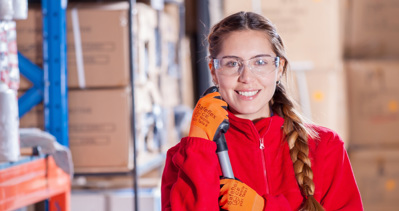 A young woman in protective goggles and gloves holds a tool and smiles at the camera