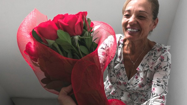 A woman smiles as she receives a large bunch of red flowers