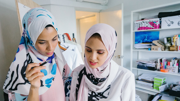 Two women wearing headscarves talk together