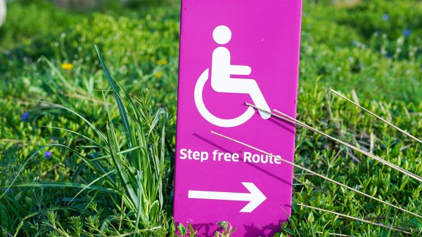 A bright pink sign that reads step free access with an arrow and a wheelchair symbol, against green grass