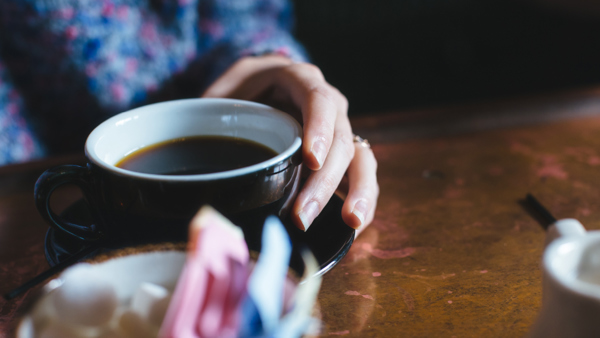 Close-up of a hand holding a cup of coffee on a wooden table
