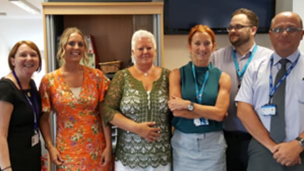A group of staff from the Bromley IAPT service stands with CEO helen mackay