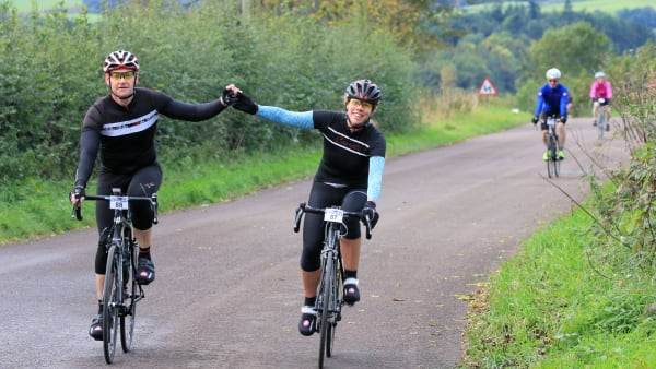 A man and a woman high-five while riding their bicycles