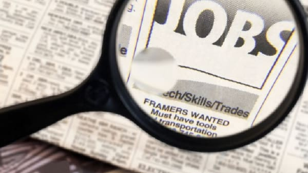 magnifying glass over a newspaper, highlighting the word jobs