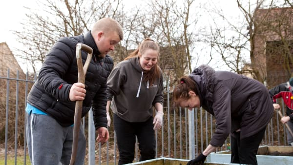 Two women and a man dig in a raised vegetable bed